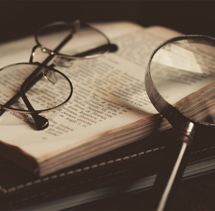 Book under glasses and magnifier