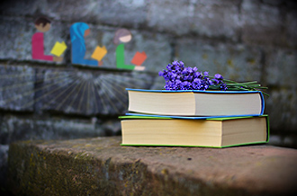 Two books stacked on a rock with brick wall behind
