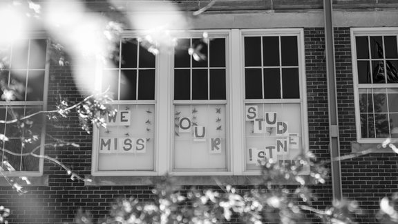 "a black and white image of an exterior window at a school. ""we miss our students"" is posted in the windows."