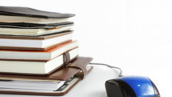Text Books stacked up on a white table next to blue and black Computer mouse