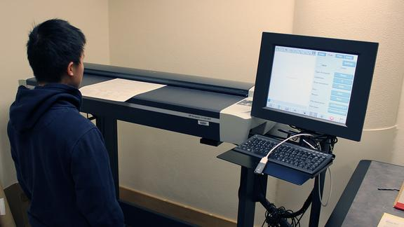 a student scans an old UMD student newspaper on a large format scanner