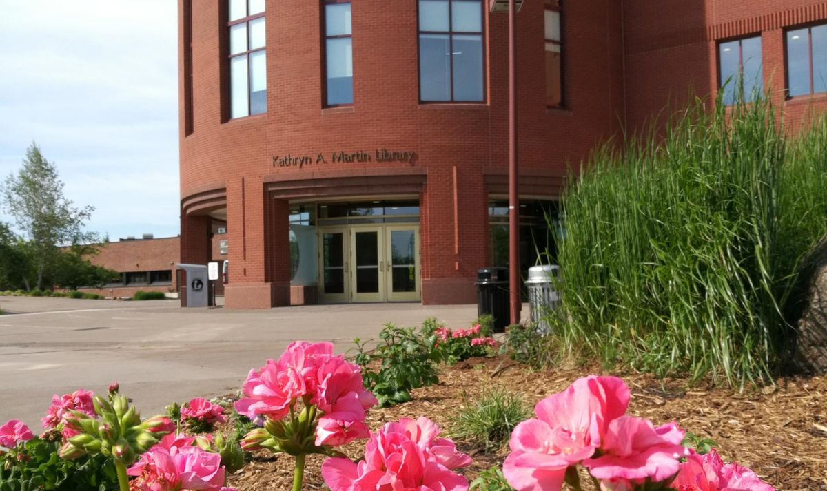 a photograph of the kathryn martin library. pink flowers are pictured in front of the library building.