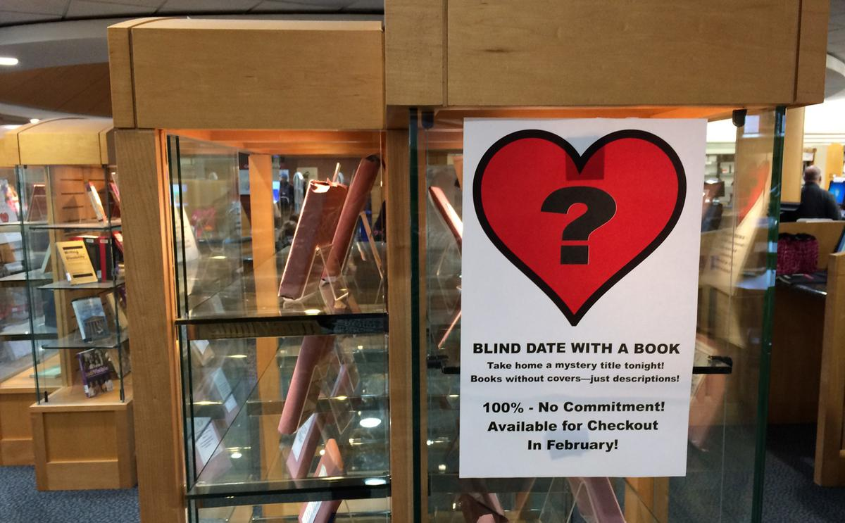 library display case showing books wrapped and sign with question mark inside heart