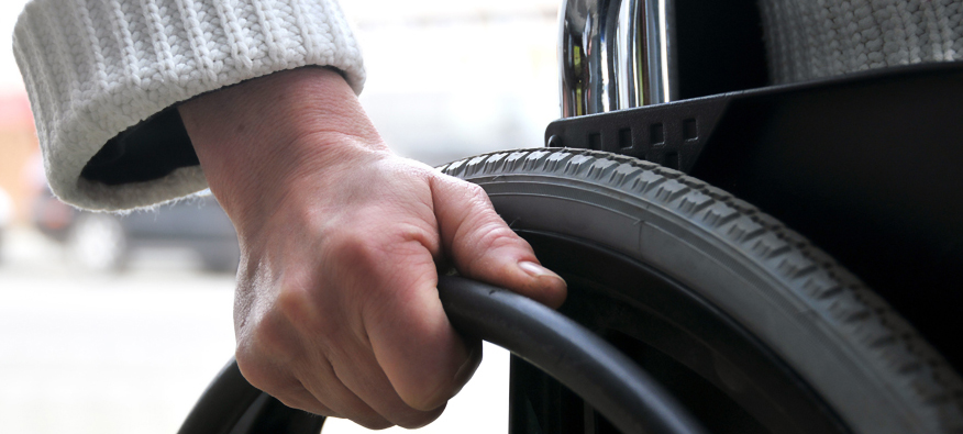 person's hand on wheelchair rim